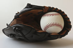 A Baseball in a Brown and Black Glove Stock Image