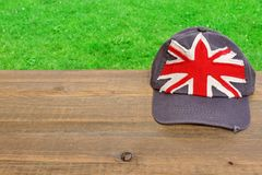 Baseball cap with British flag on wooden table Stock Image