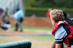 Baseball catcher leaning over dugout fence looking at camera. Royalty Free Stock Photos