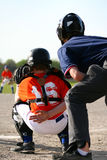 Baseball catcher and umpire. Baseball catcher waiting for pitch with umpire in back Stock Image