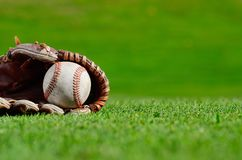 Baseball close up. Close-up of baseball and glove on the grass Royalty Free Stock Images