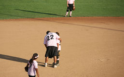 Baseball coach helping a player. Baseball coach assisting a player stock photography