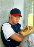Baseball is cool. Young man sits and leans back against a dugout at a baseball field.  He has on a navy, grey and red uniform Royalty Free Stock Photo
