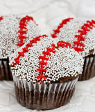 Baseball cupcakes. Three cupcakes decorated like baseballs with nonpareils and icing stitches Stock Photography