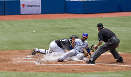 Baseball: Derek Lee slides into home. Chicago Cubs' Derek Lee avoids a tag and scores as the ball gets away from Toronto Blue Jays' catcher Rod Barajas tries to royalty free stock image