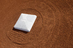 Baseball diamond base. Surrounded with groomed dirt at a school softball field Royalty Free Stock Image