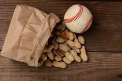 Baseball e una borsa con le arachidi che si rovesciano fuori Fotografia Stock