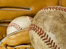 Baseball Equipment. Composition showing the typical elements of the game of baseball: a ball used in the foreground and another ball on a glove in the background Royalty Free Stock Photo
