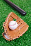 Baseball equipment against grass Stock Photos