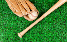 Baseball equipment on artificial green grass turf field Stock Photos
