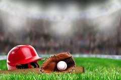 Baseball Equipment on Grass With Copy Space. Low angle view of baseball helmet, bat, glove and ball on field grass and deliberate shallow depth of field on stock image