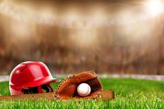 Baseball Equipment on Grass With Copy Space. Low angle view of baseball helmet, bat, glove and ball on field grass and deliberate shallow depth of field on Stock Photo