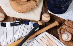 Baseball Equipment. High angle shot of baseball gear on a rustic wood surface. Items include, Home Plate, helmet, baseball, ball, glove, catchers mitt, score Royalty Free Stock Image