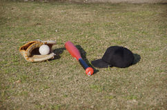 Baseball equipment for kids. A baseball glove, a ball, a bat and a cap for kids Stock Photo