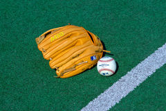 Baseball equipment. ZAGREB , CROATIA - 13 AUGUST 2015 -  official Major League Baseball ball and glove on the green field , product shot Royalty Free Stock Image