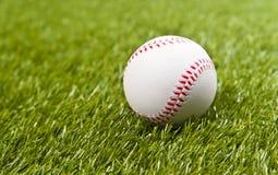 Baseball on the fake green grass Stock Photos