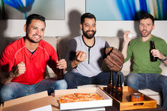 Baseball fans rooting for their team. Portrait of a group of baseball fans and friends watching a game on TV at night and feeling excited Stock Photo