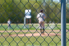 Baseball Fence. A chain link baseball fence with a blurred out backdrop of a baseball game going on Stock Photo
