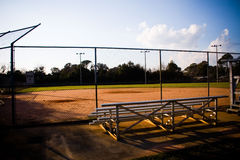 Baseball Field Empty. Empty baseball field with bleachers. High contrast image with dark shadows and blue sky Royalty Free Stock Photos