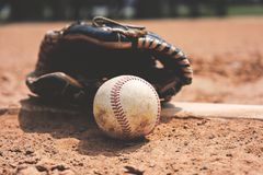 Baseball on field with glove close up in dirt. stock images