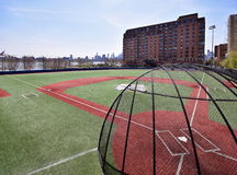 Baseball field in New Jersey. Empty little league baseball field with partial Manhattan skyline blurred in the background Stock Images