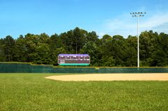 Baseball field and Scoreboard. Baseball field with green grass, fence, blue sky, tree line and outfield and infield Stock Photos