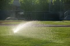 Baseball field sprinkler waters the grass, pointed right on a sunny day Royalty Free Stock Photo