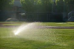 Baseball field sprinkler waters the grass, pointed right on a sunny day. Baseball field sprinkler waters the grass, pointed right Royalty Free Stock Photo
