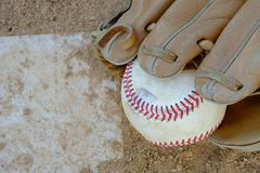 A baseball in a first basemans glove or mitt sits on the home pl Stock Photography