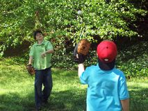 Baseball in flight. Two brothers playing baseball in backyard on a spring day Royalty Free Stock Photos