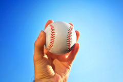 Baseball game. Baseball ball holding by hand against blue clean sky Stock Images