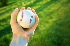 Baseball game. Baseball ball holding by hand against green fresh grass Stock Photography