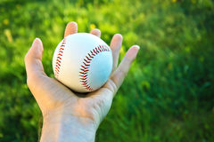 Baseball game. Baseball ball holding by hand against green fresh grass Royalty Free Stock Image