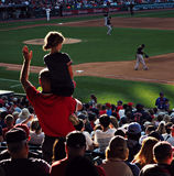 Baseball Game in Cleveland. Fans watch a baseball game between Cleveland and Miami. A father holds his daughter to watch Stock Photo