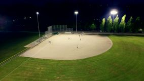 Baseball game on a field at a park in the evening. Beautiful, breathtaking, cinematic aerial shot of people playing basketball at a field in the evening