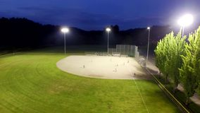 Baseball game on a field at a park in the evening stock footage