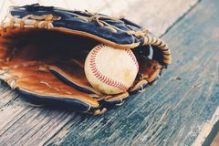 Baseball and glove on dugout bench Stock Photo