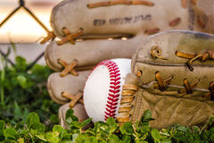 Baseball game mitt and ball. Old worn baseball glove / mitt and old ball on grass in front of the fence of the baseball field Royalty Free Stock Photos