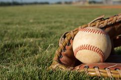 Baseball in a Glove. On the field Royalty Free Stock Photos