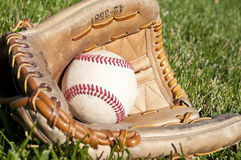 Baseball glove. A baseball and leather glove on green grass Royalty Free Stock Images