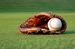 Baseball glove. Close up of a well worn baseball glove on the field Stock Image
