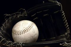 Baseball Glove. Well used softball and a black baseball glove, isolated on a black background Royalty Free Stock Photography