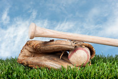 Baseball glove. Ball, and bat laying on grass against a blye, lightly cloudy sky for placement of copy Royalty Free Stock Image