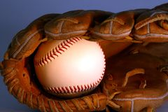 Baseball in glove. On background with warm light Royalty Free Stock Photos