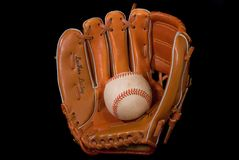 Baseball In Glove. Black iso. view of baseball being caught in a baseball glove Royalty Free Stock Photo