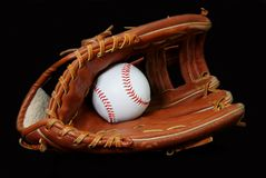 Baseball in Glove. Isolated on black background Stock Photo