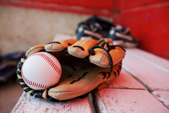 Baseball glove. A baseball and glove on a bench in the dugout Royalty Free Stock Photo