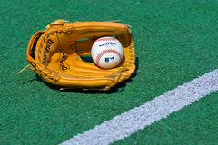 Baseball glove and ball on the field. ZAGREB , CROATIA - 13 AUGUST 2015 -  official Major League Baseball ball and glove on the green field , product shot Royalty Free Stock Photos