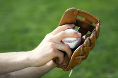 Baseball glove and ball. Male hands are holding baseball glove and ball on green background Royalty Free Stock Photo