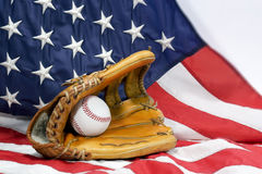 Baseball Glove, Ball & USA Flag. A well worn baseball glove holding baseball with USA flag in background Stock Photo
